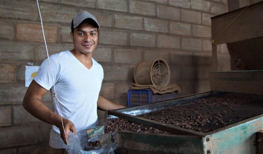 Llenando una bolsa con granos de cacao secos en la cooperatia UNOCACE.